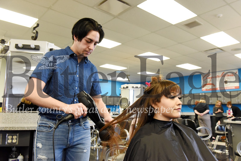 Harold Aughton/Butler Eagle: Zack Kline, 12th grade, works on voluneteer Lexy Hernandez's hair during a recent hair styling class at Butler Vo-tech.