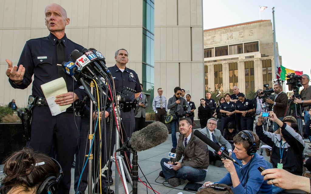. Los Angeles Police Commander Andrew Smith, left, briefs the media about the shootout scene in Big Bear that allegedly involves triple-murder suspect Christopher Jordan Dorner, during a news conference in front of the Police Administration Building in Los Angeles Tuesday, Feb. 12, 2013. (AP Photo/Damian Dovarganes)