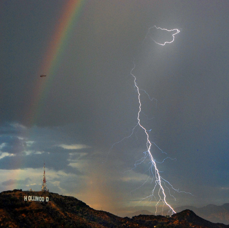 . A rainbow and bolts of lightning are shown next to the Hollywood sign Sept. 29, 2010 in Los Angeles, Calif. Days of historic heat in Southern California are ending with scattered thunderstorms and lightning strikes that raise the risk of wildfires in the region. (AP Photo/Mike Meadows)