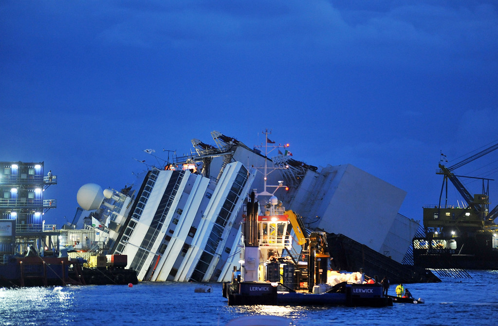 . Titan and Micoperi workers are seen next to the stricken Costa Concordia on September 16, 2013 in Isola del Giglio, Italy. Work begins today to right the stricken Costa Concordia vessel, which sank on January 12, 2012. If the operation is successful, it will then be towed away and scrapped. The procedure, known as parbuckling, has never been carried out on a vessel as large as Costa Concordia before. (Photo by Laura Lezza/Getty Images)