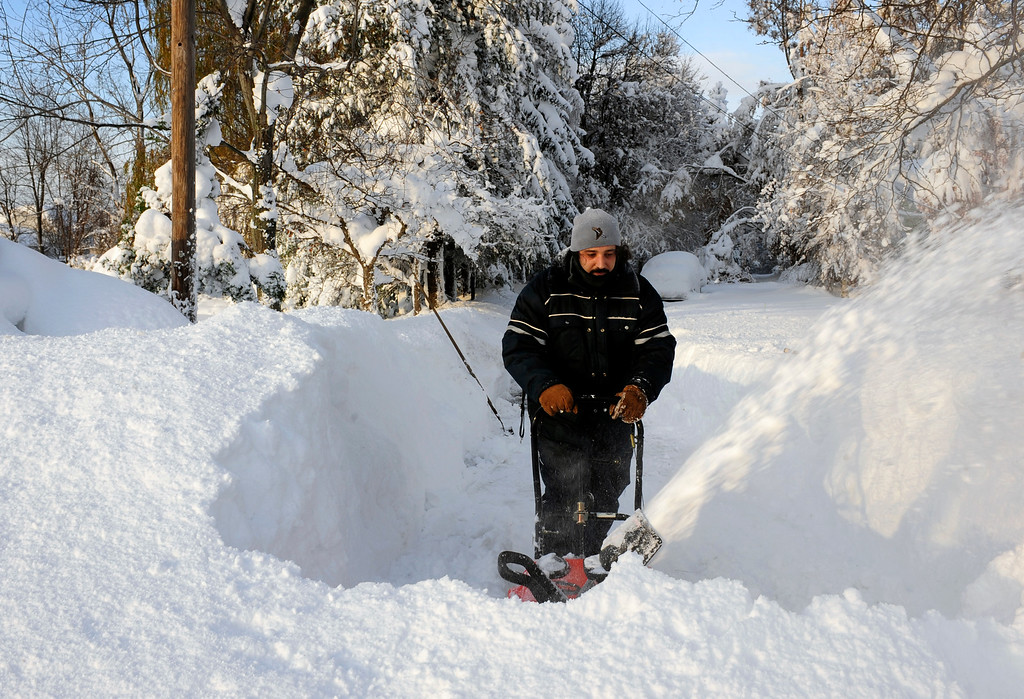 . Bob Wilcox clears the snow at the end of his driveway on Bowen Rd. in Lancaster,  N.Y. Wednesday, Nov. 19, 2014.  A ferocious storm dumped massive piles of snow on parts of upstate New York, trapping residents in their homes and stranding motorists on roadways, as temperatures in all 50 states fell to freezing or below.   (AP photo/Gary Wiepert)