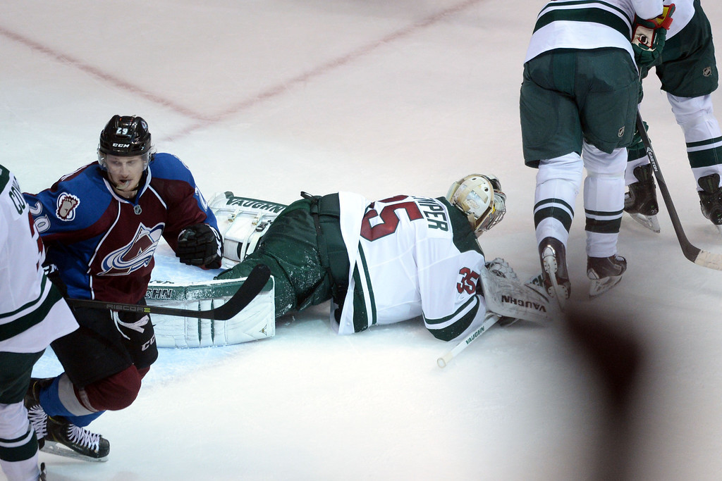 . DENVER, CO - APRIL 26: Jonas Brodin (25) of the Minnesota Wild falls to the ice after a game-tying goal by P.A. Parenteau (15) of the Colorado Avalanche (not pictured) as Nathan MacKinnon (29) celebrates during the third period. The Colorado Avalanche hosted the Minnesota Wild during game five of the first round of the NHL Stanley Cup Playoffs at the Pepsi Center on Saturday, April 26, 2014. (Photo by Karl Gehring/The Denver Post)