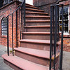 Brick staircase with black metal hand rails leading to the front door of large home.