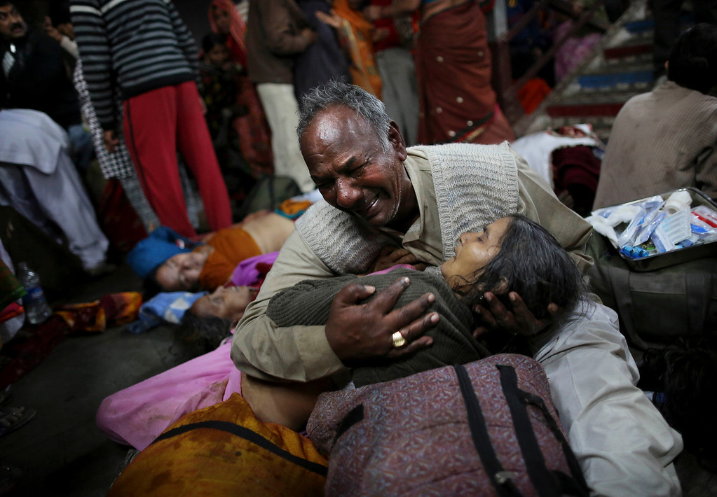 . An Indian man weeps as he holds his wife who was killed in a stampede on a railway platform at the main railway station in Allahabad, India, Sunday, Feb. 10, 2013.   (AP Photo/Kevin Frayer)