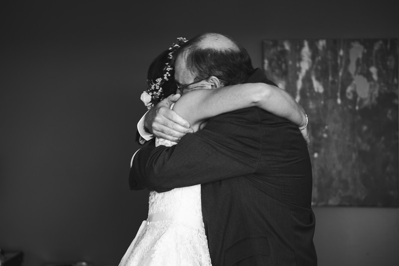 Bride and her father hugging tightly.