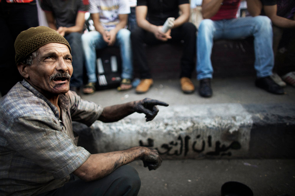 Description of . An Egyptian man gestures near graffiti he painted on a pavement that reads in Arabic: