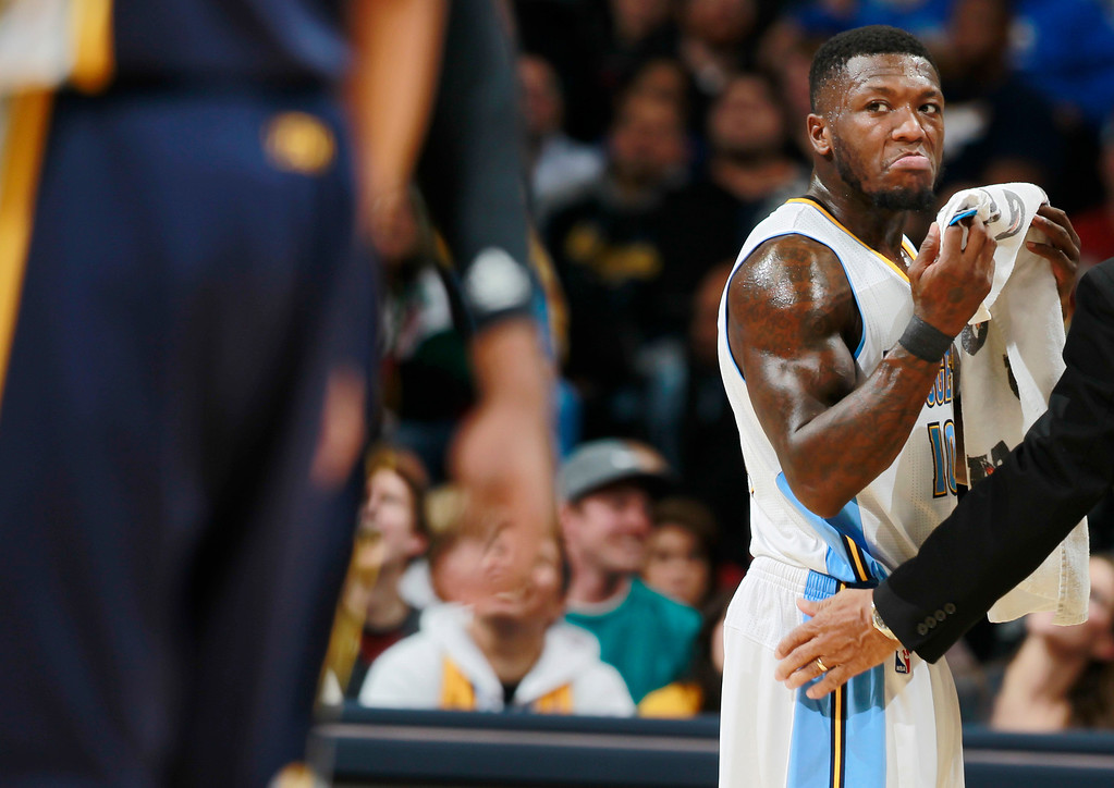 . Denver Nuggets guard Nate Robinson, back, glares at Utah Jazz players after Robinson was called for a foul before a time out in the fourth quarter of Utah\'s 103-93 victory in an NBA basketball game in Denver on Friday, Dec. 13, 2013. (AP Photo/David Zalubowski)