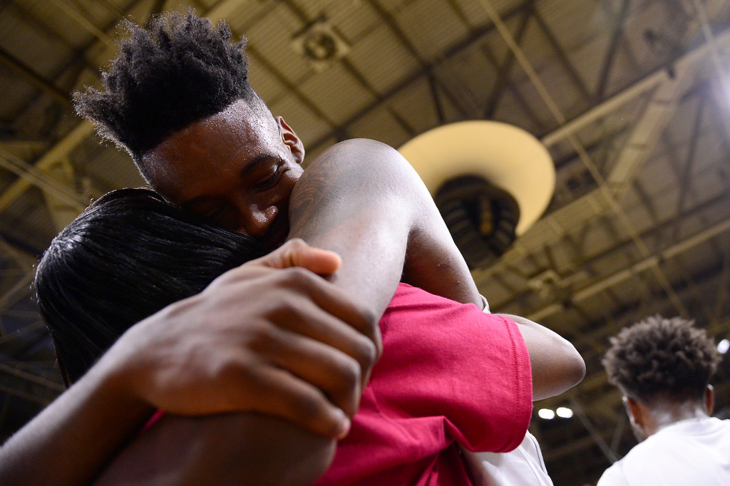 . De\'ron Davis (20) of Overland Trailblazers hugs his mother, Terri Latson, after defeating Eaglecrest Raptors at the Coors Events Center on March 12, 2016 in Boulder, Colorado. Overland Trailblazers defeated Eaglecrest Raptors 66-56 to win the Colorado State 5A Basketball Championship.  (Photo by Brent Lewis/The Denver Post)