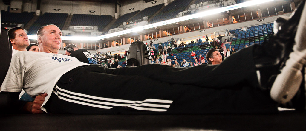 . Lynx assistant coach Jim Petersen stretches out on stage while watching a film about his team\'s season during the team\'s WNBA championship pep rally. (Pioneer Press: Ben Garvin)