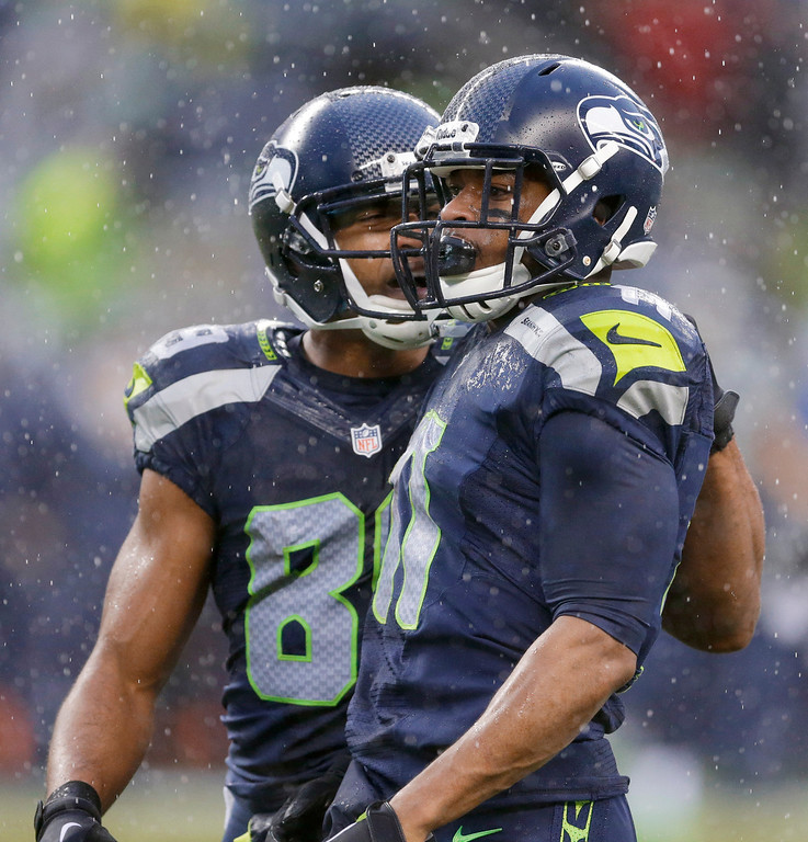 . Seattle Seahawks wide receiver Percy Harvin, right, celebrates after catching a pass with wide receiver Doug Baldwin during the second quarter of an NFC divisional playoff NFL football game against the New Orleans Saints in Seattle, Saturday, Jan. 11, 2014. (AP Photo/Ted S. Warren)