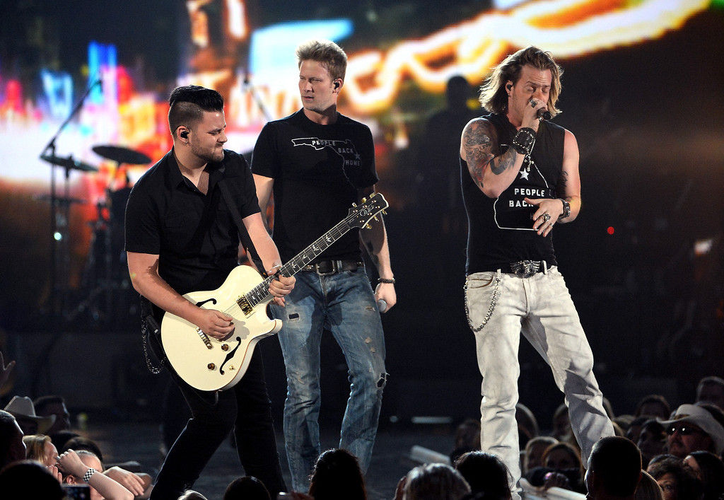 . Singers Brian Kelley (C) and Tyler Hubbard (R) of Florida Georgia Line perform onstage during ACM Presents: An All-Star Salute To The Troops at the MGM Grand Garden Arena on April 7, 2014 in Las Vegas, Nevada.  (Photo by Ethan Miller/Getty Images for ACM)