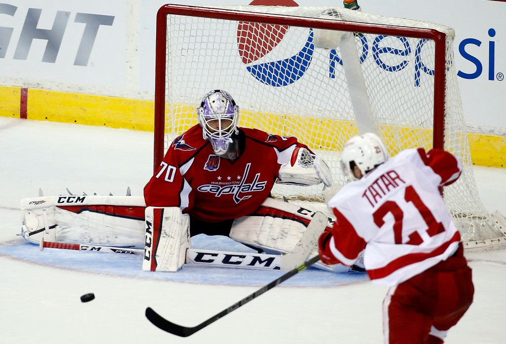 . Washington Capitals goalie Braden Holtby (70) prepares to block a shot by Detroit Red Wings left wing Tomas Tatar (21), from Slovakia, in the third period of an NHL hockey game, Wednesday, Oct. 29, 2014, in Washington. The Red Wings won 4-2. (AP Photo/Alex Brandon)
