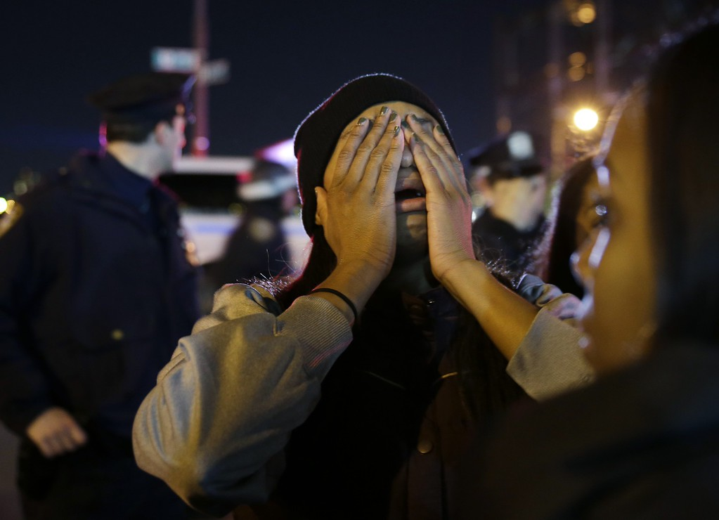 . A woman is overcome with emotion during a protest against the grand jury\'s decision in the Eric Garner case in Times Square in New York, Wednesday, Dec. 3, 2014. The grand jury cleared a white New York City police officer Wednesday in the videotaped chokehold death of Garner, an unarmed black man, who had been stopped on suspicion of selling loose, untaxed cigarettes, a lawyer for the victim\'s family said. (AP Photo/Seth Wenig)