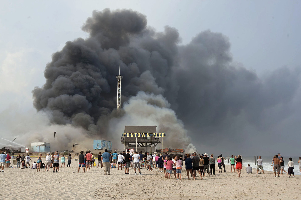 . Onlookers watch from the shore as black smoke rises from a fire on the Seaside Heights, N.J. boardwalk Thursday, Sept. 12, 2013. The fire started in the vicinity of an ice cream shop and burned several blocks of boardwalk and businesses in a town that was still rebuilding from damage caused by Superstorm Sandy. (AP Photo/The Asbury Park Press, Bob Bielk)