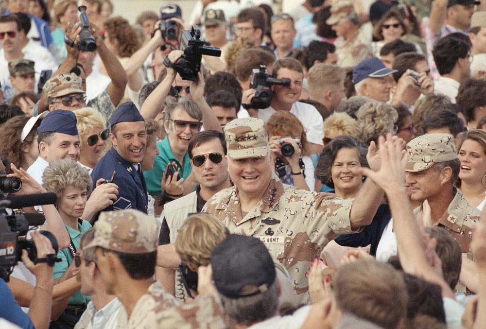 Description of . Gen. H. Norman Schwarzkopf, center, waves as he makes his way through the crowd during welcoming ceremonies on Sunday, April 21, 1991 at MacDill Air Force Base in Tampa, Fla. Schwarzkopf was given a heroes welcome after returning from eight months in the Persian Gulf .Directly behind the General is his wife Brenda. (AP Photo/Lynne Sladky)