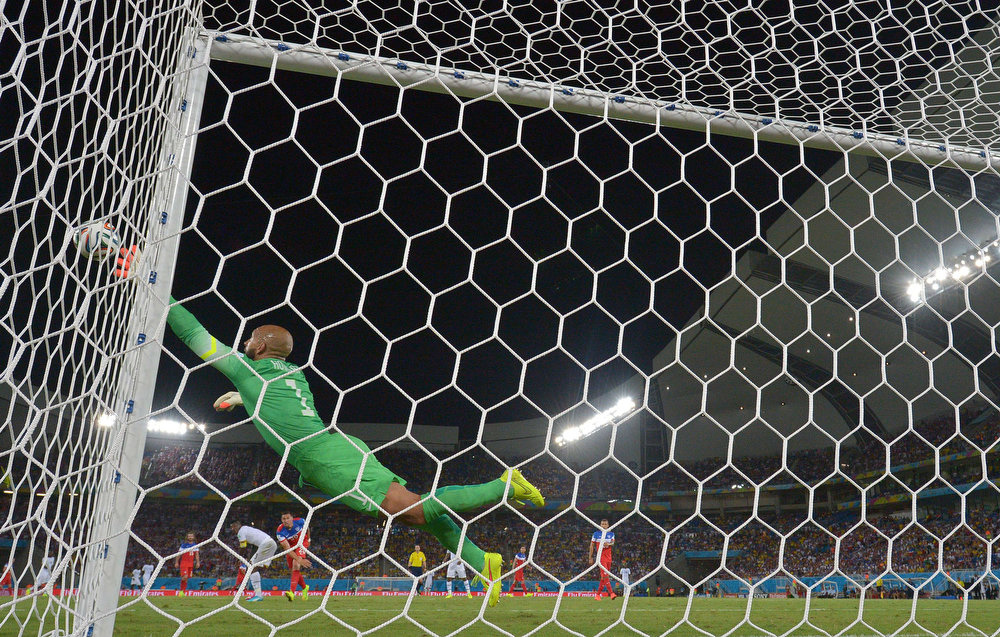 Description of . US goalkeeper Tim Howard dives for the ball during a Group G football match between Ghana and US at the Dunas Arena in Natal during the 2014 FIFA World Cup on June 16, 2014.  AFP PHOTO / CARL DE SOUZACARL DE SOUZA/AFP/Getty Images