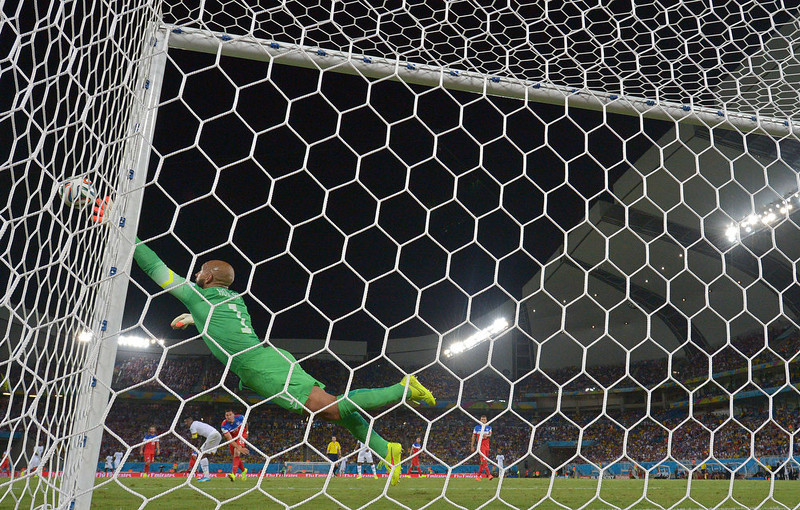 . US goalkeeper Tim Howard dives for the ball during a Group G football match between Ghana and US at the Dunas Arena in Natal during the 2014 FIFA World Cup on June 16, 2014.  AFP PHOTO / CARL DE SOUZACARL DE SOUZA/AFP/Getty Images