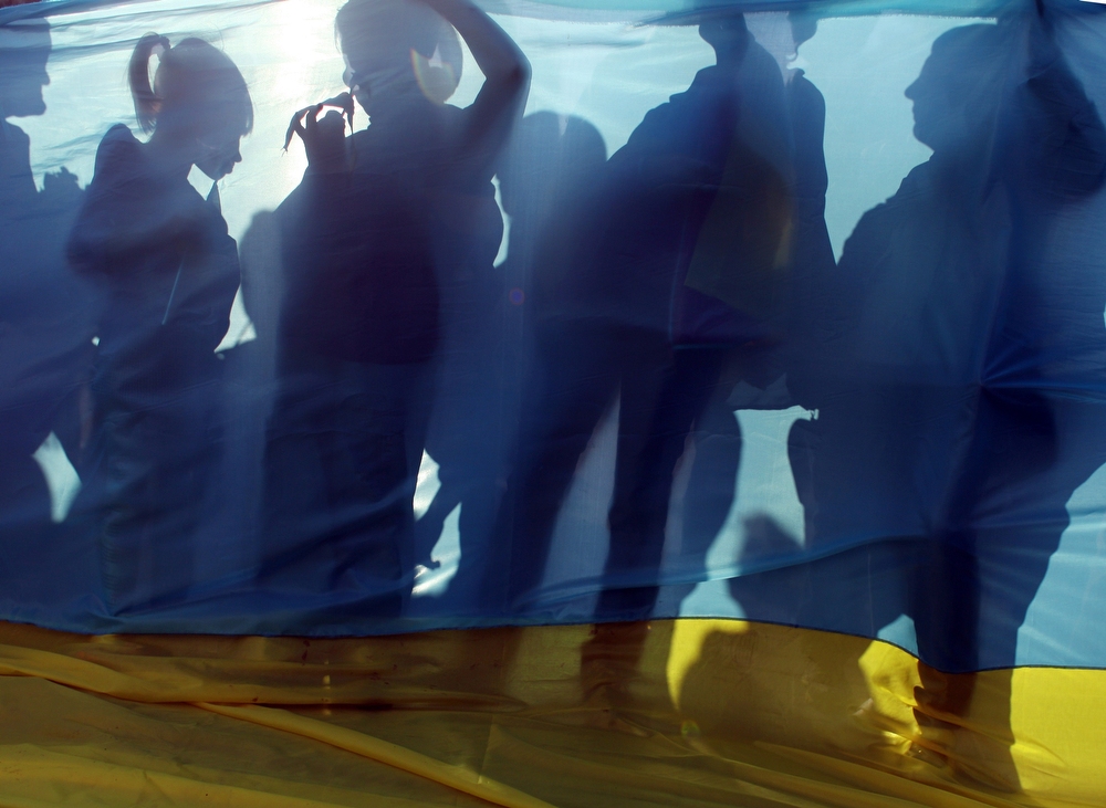 . The shadows of Pro-Ukrainian supporters is seen as they stand holding a giant Ukrainian flag during a rally in the southern Ukrainian city of Mariupol on April 23, 2014. The first American troops arrived in Poland Wednesday, after Washington said it was sending a force of 600 to the Baltic states as the crisis over Ukraine deepens. Some 150 soldiers from the 173rd Airborne Brigade touched down early afternoon in Swidwin, in the northeast of the country, according to an AFP journalist at the scene. (ANATOLII STEPANOV/AFP/Getty Images)