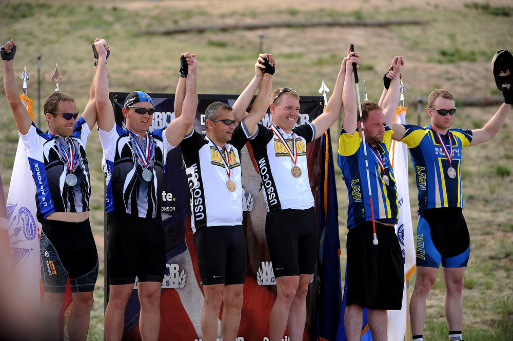. The winners of the Men\'s 30K Tandem race hold up their hands after receiving their medals. The fourth annual Warrior Games cycling event took started and finished at Falcon Stadium on the grounds of the Air Force Academy in Colorado Springs, CO on May 12, 2013.  HRH Prince Harry was on hand to start the race as well as to hand out medals at the finish line.   A total of 260 wounded, ill and injured service members and veterans came to compete in the week long games.  Members of the Army, Marine Corps, Navy/Coast Guard/Air Force. Special Operations and the British Armed Forces all took part in the competition.  Other events included in the Warrior Games are shooting, sitting volleyball, track & field and wheelchair basketball.  (Photo by Helen H. Richardson/The Denver Post)