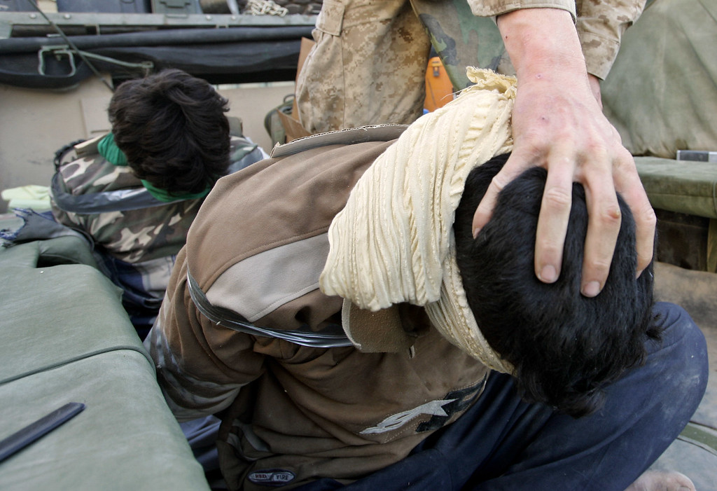 . A US Marine of the 1st Division arrests Iraqi men in the western part of Fallujah, Iraq, Saturday, Nov. 13, 2004. About 80 percent of the city was said to be under U.S. control, with insurgents pushed into a narrow corner.  (AP Photo/Anja Niedringhaus)