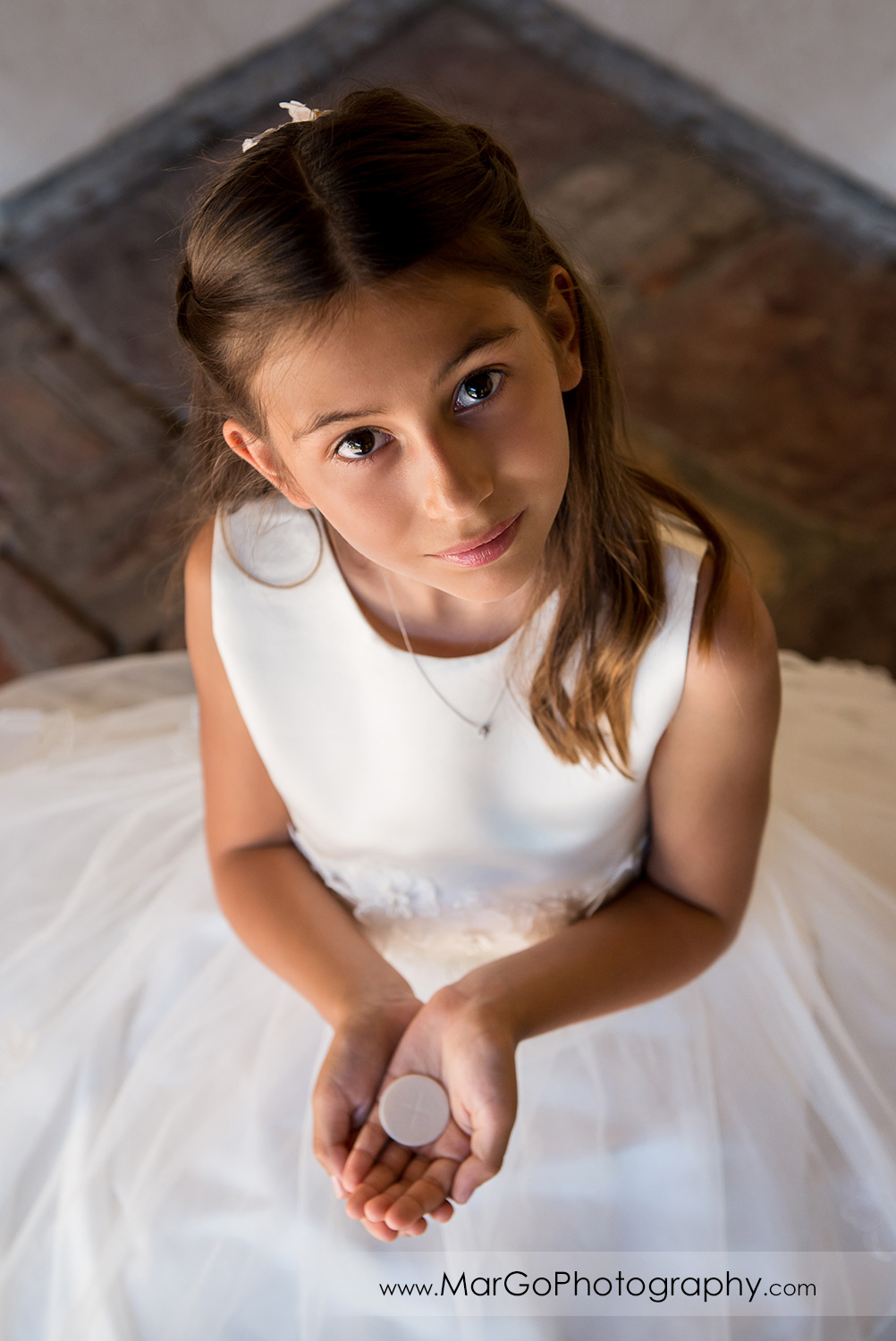 first communion girl in white dress holding wafer and looking into camera at Cafe Wisteria in Menlo Park