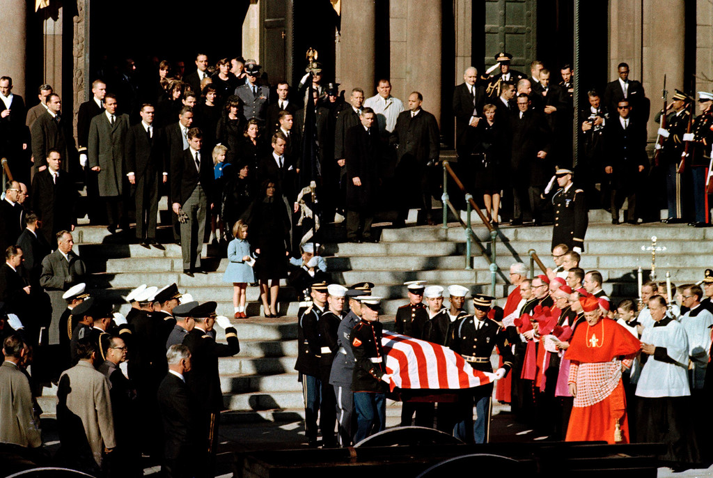 . Representatives of all branches of the military act as pall bearers during the funeral of President John F. Kennedy as they leave following funeral services at St. Matthew\'s Cathedral in Washington, Nov. 25, 1963. Behind them are members of the Kennedy family, with widow Jacqueline Kennedy in front holding the hands of her young children, Caroline, left, and John Jr. The president\'s brothers, Sen. Edward M. Kennedy (D-Mass.) and Attorney General Robert F. Kennedy are behind her with other members of the family around them.   (AP Photo)