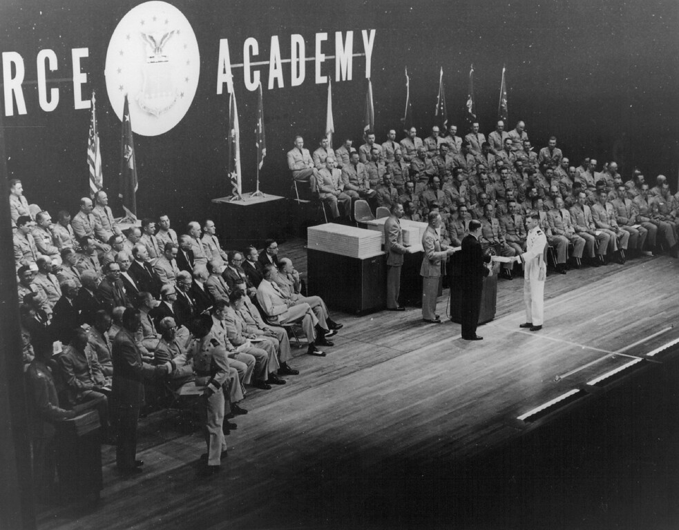 . THE FIRST GRADUATION � At right, Secretary of the Air Force James H. Douglas presents his diploma to a graduating cadet of the Class of 1959, the first class to graduate from the Air Force Academy. At left, another cadet receives his commission as a second lieutenant in the Air Force from Air Force Chief of Staff General Thomas D. White. The ceremonies took place in Harmon Hall at the Academy\'s permanent site near Colorado Springs. The Denver Post Library Archive