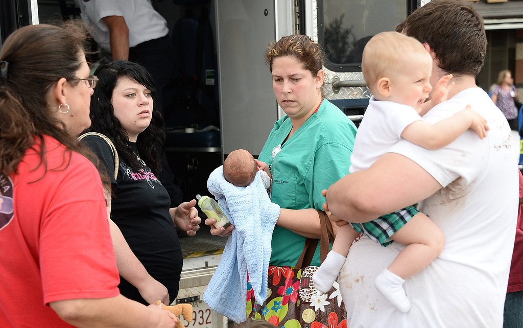 . A nurse holds a baby waiting to be checked out by paramedics at the IMAX theater that was used as a triage area. Moore hospital was destroyed after being hit by a tornado that destroyed buildings and overturned cars. 