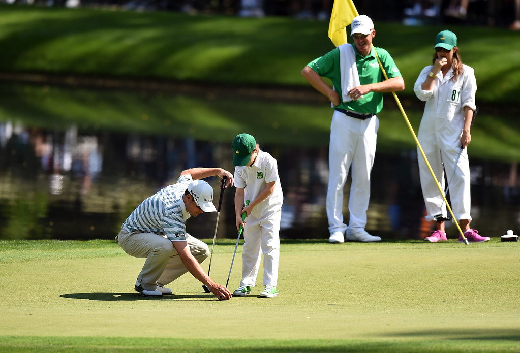 . Zach Johnson of the US helps his son to line up a putt during the Par 3 Contest prior the start of the 78th Masters Golf Tournament at Augusta National Golf Club on April 9, 2014 in Augusta, Georgia. Augusta National\'s trademark back-nine drama in the final round of the Masters could reach epic heights Sunday with a field that offers no clear favorite and several rising young stars.    JIM WATSON/AFP/Getty Images