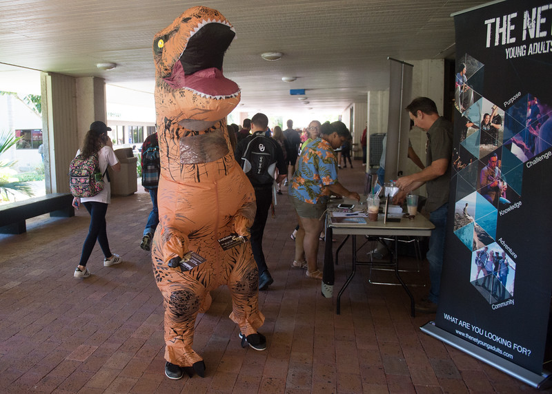Students (and one T-Rex) with the Net Young Adults student organization engage with passersby in the university breezeway as they pass out information about upcoming events.