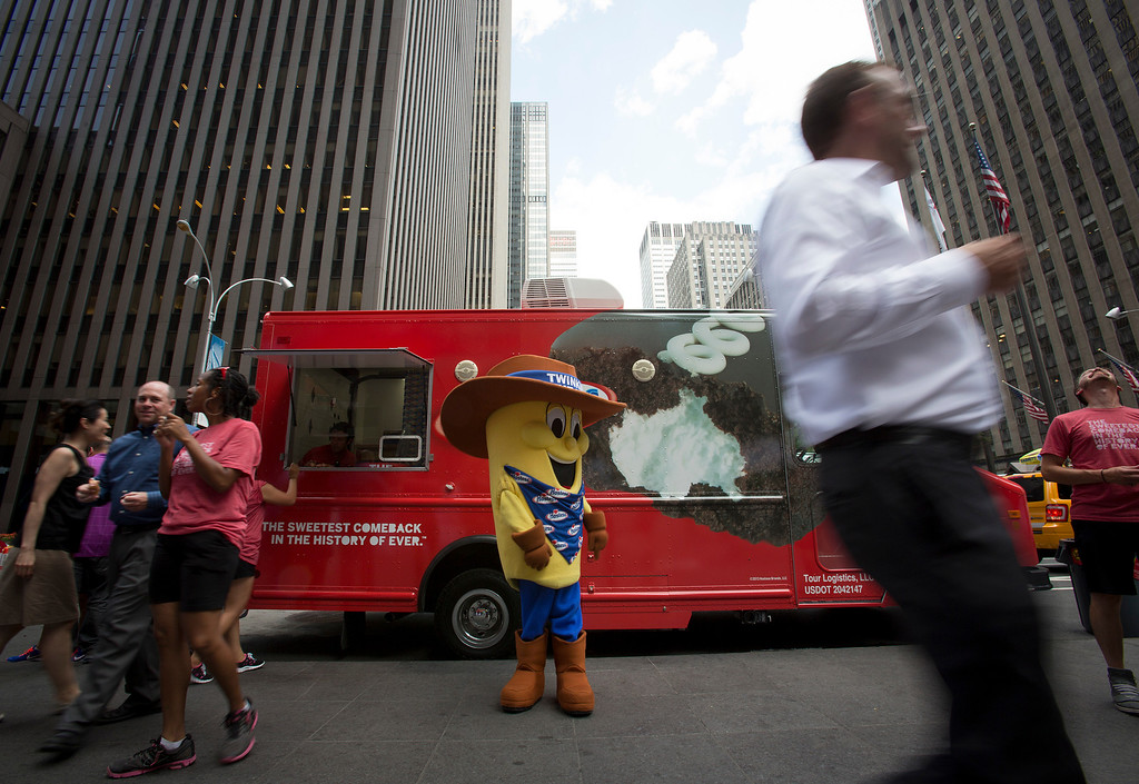 . Pedestrians pass in front of a Hostess Brands LLC truck handing out Twinkies snack cakes as part of a promotion in New York, U.S., on Monday, July 15, 2013. Photographer: Scott Eells/Bloomberg