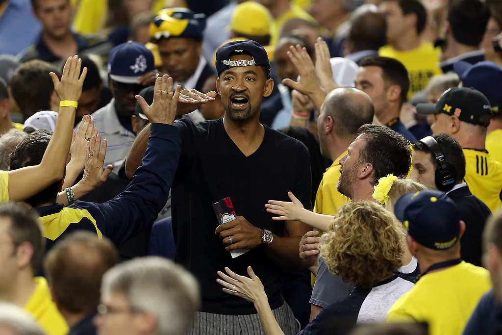 . Former Michigan Wolverines player Juwan Howard greets Michigan fans in the stands against the Louisville Cardinals during the 2013 NCAA Men\'s Final Four Championship at the Georgia Dome on April 8, 2013 in Atlanta, Georgia.  (Photo by Andy Lyons/Getty Images)