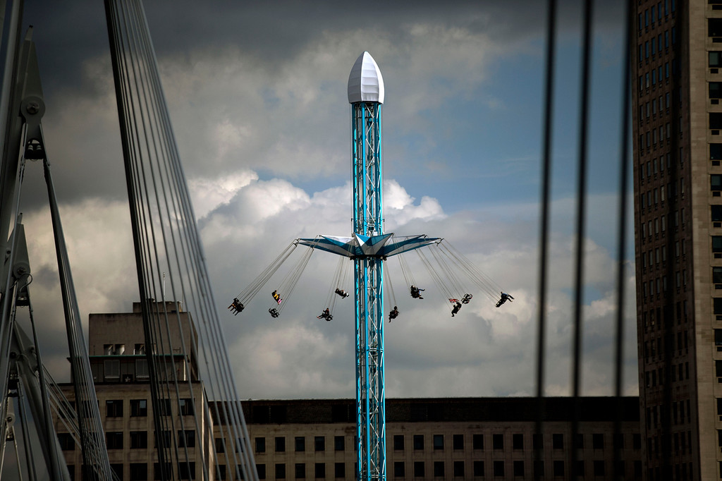 . People are spun round on a fairground ride on the south bank of the River Thames in London, Thursday, Sept. 27, 2012.  (AP Photo/Matt Dunham)