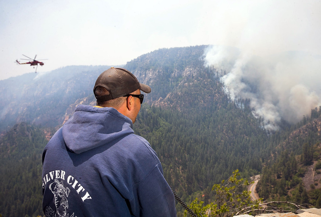 . A Sante Fe Hot Shot works as a lookout as he oversees part of the Slide Fire in Sterling Canyon at the Oak Creek Overlook above Sedona, Ariz., on Thursday, May 22, 2014. Hundreds of firefighters worked Thursday to protect communities on the edge of Flagstaff from a wildfire that is chewing up a scenic Arizona canyon with towering flames and burning entire trees down to nothing but ash. (AP Photo/The Arizona Republic, Michael Schennum)