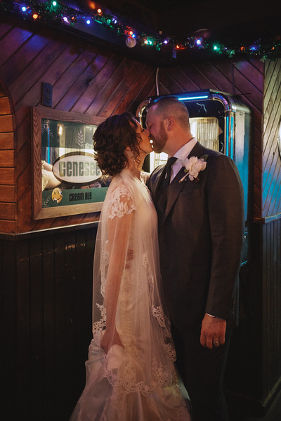 The bride and groom kiss in the corner of a dimly lit dive bar with Christmas lights above them and a beer sign and jukebox in the background.