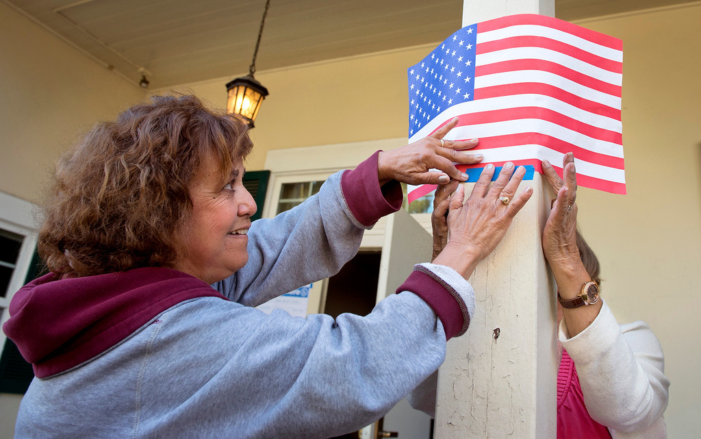 . Poll worker Gloria Gomez tapes up a flag marking the polling entrance at the Greenleaf Masonic Temple on Beverly Boulevard in Whittier, Calif. Tuesday morning June 3, 2014.   (Staff photo by Leo Jarzomb/Whittier Daily News)