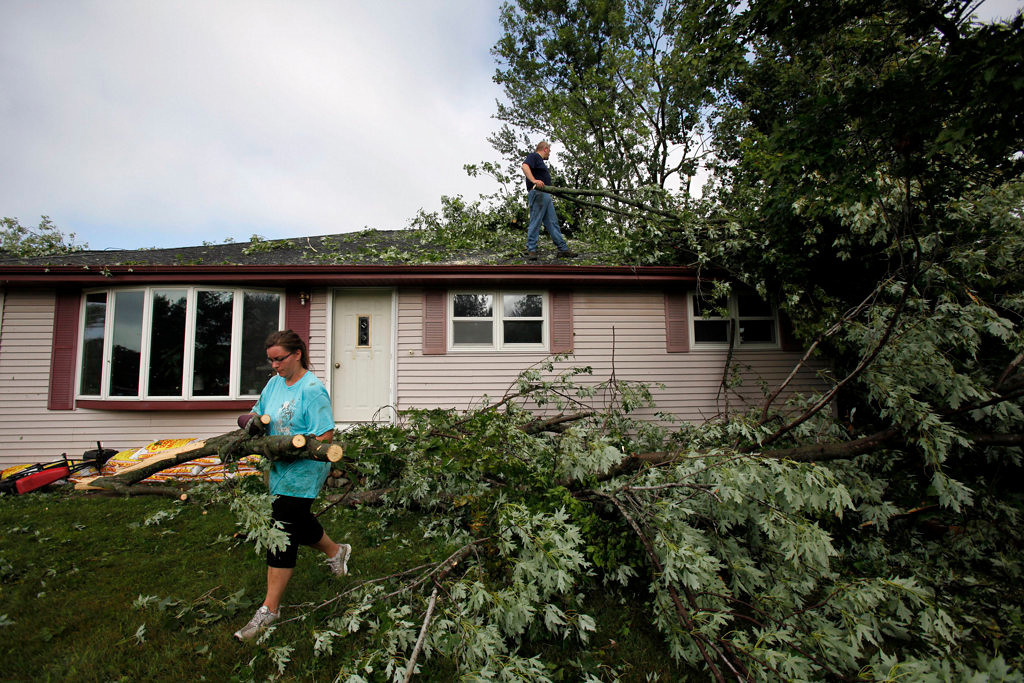 . Friends and family help clean up damage to Kristi Otto and Betsy Sadenwassen\'s home in Hortonville, Wis., after Tuesday night\'s storms, which packed winds of more than 100 mph. (AP Photo/The Post-Crescent, Sharon Cekada)