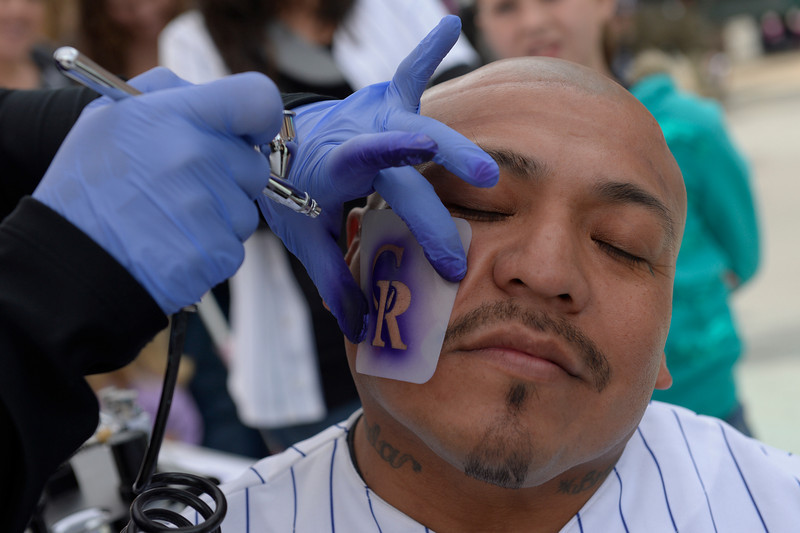 . Julio Poot Goomez of Denver gets his face painted before the game. The Colorado Rockies hosted the Arizona Diamondbacks in the Rockies season home opener at Coors Field in Denver, Colorado Friday, April 4, 2014. (Photo by Craig F. Walker/The Denver Post)