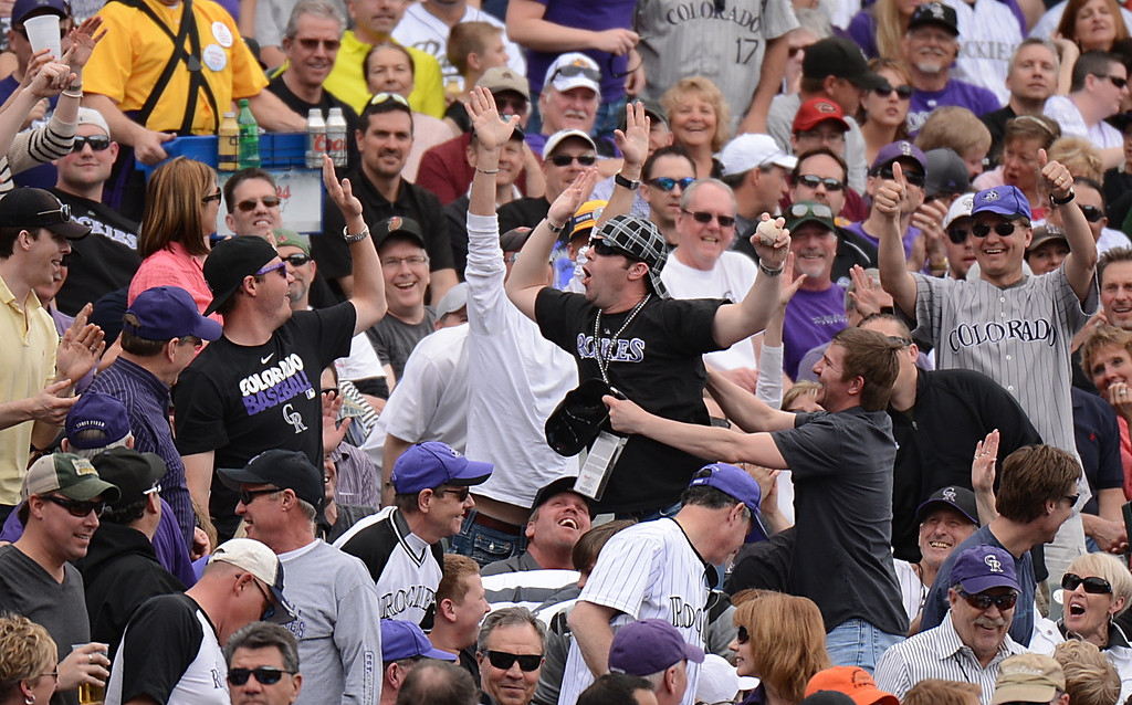 . A fan celebrates in the stands after catching a foul ball.  (Photo by Hyoung Chang/The Denver Post)