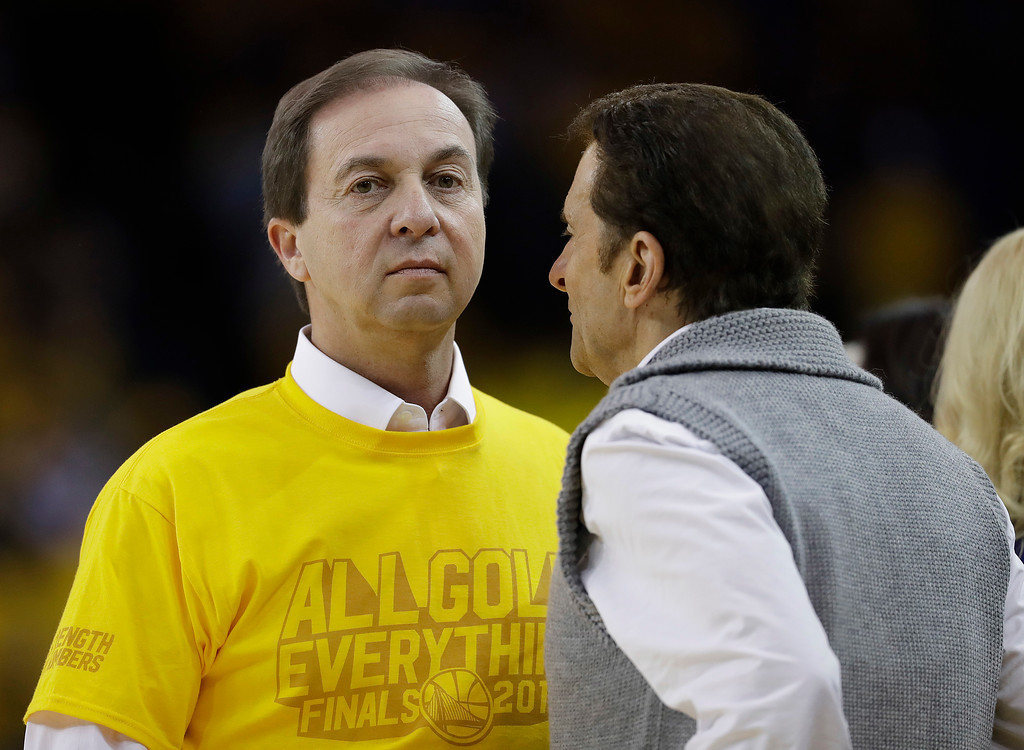 . Golden State Warriors owners Joe Lacob, left, talks with Peter Guber during the second half of Game 2 of basketball\'s NBA Finals between the Warriors and the Cleveland Cavaliers in Oakland, Calif., Sunday, June 4, 2017. (AP Photo/Marcio Jose Sanchez)