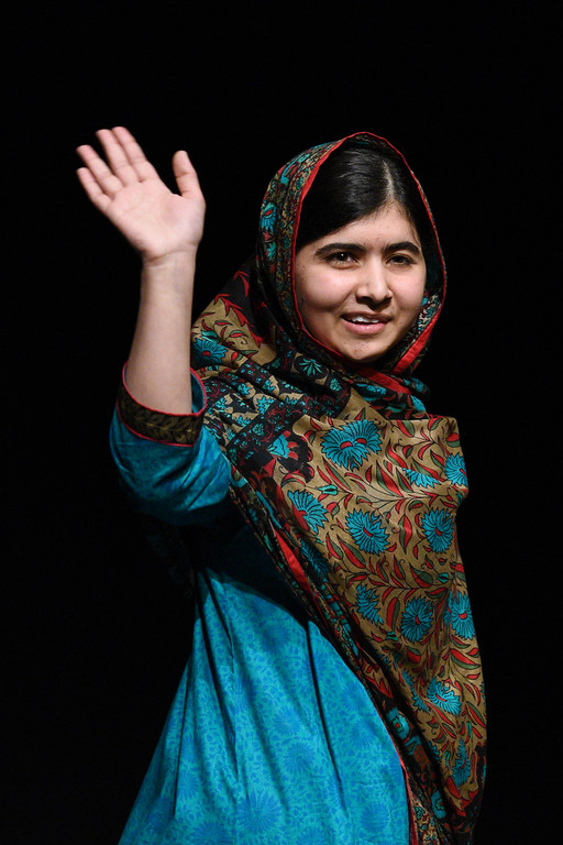 """. Pakistani rights activist Malala Yousafzai waves after addressing the media in Birmingham, central England on October 10, 2014. The Nobel Peace Prize went Friday to 17-year-old Pakistani Malala Yousafzai and India\'s Kailash Satyarthi for their work promoting children\'s rights. Seventeen-year-old Nobel Peace Prize winner Malala Yousafzai said she was \""""honoured\"""" to be the first Pakistani and the youngest person to be given the award and dedicated the award to the \""""voiceless\"""". \""""This award is for all those children who are voiceless, whose voices need to be heard,\"""" she said. AFP PHOTO / OLI SCARFF/AFP/Getty Images"""