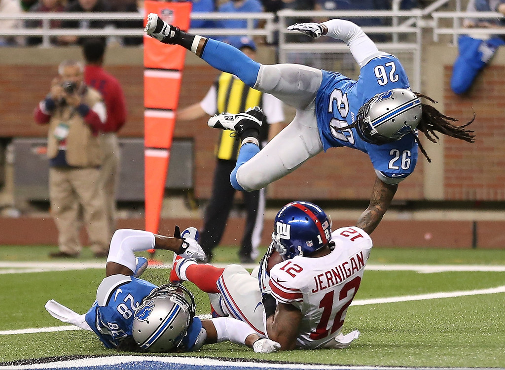 . Jerrel Jemigan #12 of the New York Giants scores on a 20 yard touchdown pass from Eli Manning #10 during the second quarter of the game as Louis Delmas #26 and Bill Bentley #28 of the Detroit Lions attempts to defend on December 22, 2013 in Detroit, Michigan.  (Photo by Leon Halip/Getty Images)