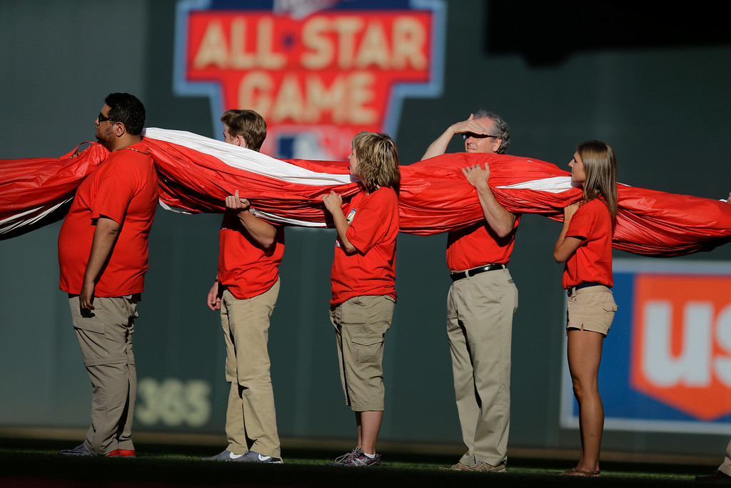 . The U.S. flag is carried on the field before the MLB All-Star baseball game, Tuesday, July 15, 2014, in Minneapolis. (AP Photo/Jeff Roberson)
