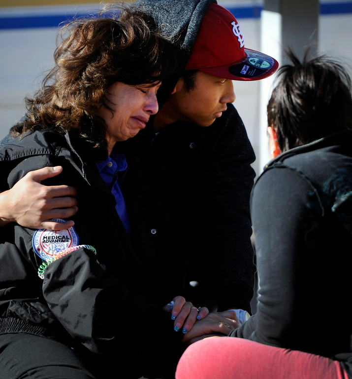. A women is consoled by a young man at the scene of shooting at 16005 Ithaca Place in Aurora Saturday afternoon. The bodies of four people, including a gunman are dead at the scene following a standoff situation early Saturday morning. The Denver Post/ Andy Cross