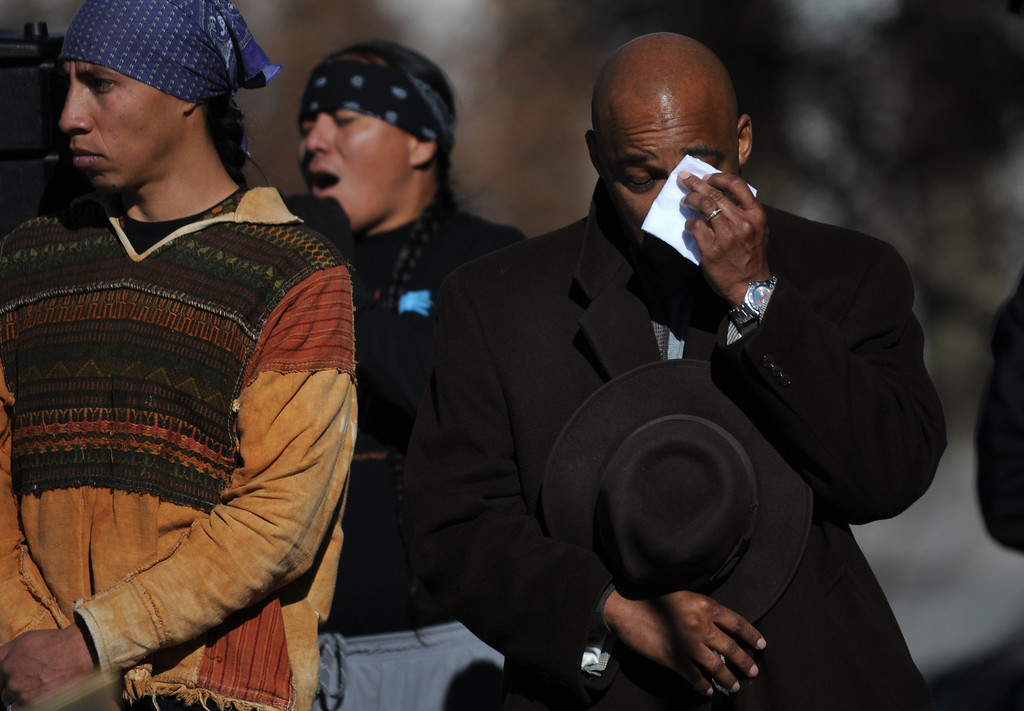 . DENVER, CO--NOVEMBER 26, 2011-- From left, Siri Martinez and Derek Brown stand next to Mayor Michael Hancock as he wipes his eyes while they listen to a prayer song being sung after a brutal account of the Sand Creek Massacre was read to the audience Nov. 26, 2011 during the final day of the 13th Annual Sand Creek Massacre Spiritual Healing Run in Denver that started at the Sand Creek Massacre National Historic Site and ended on the west steps of the State Capitol Building.   Photo by Leah Millis/Special to The Denver Post