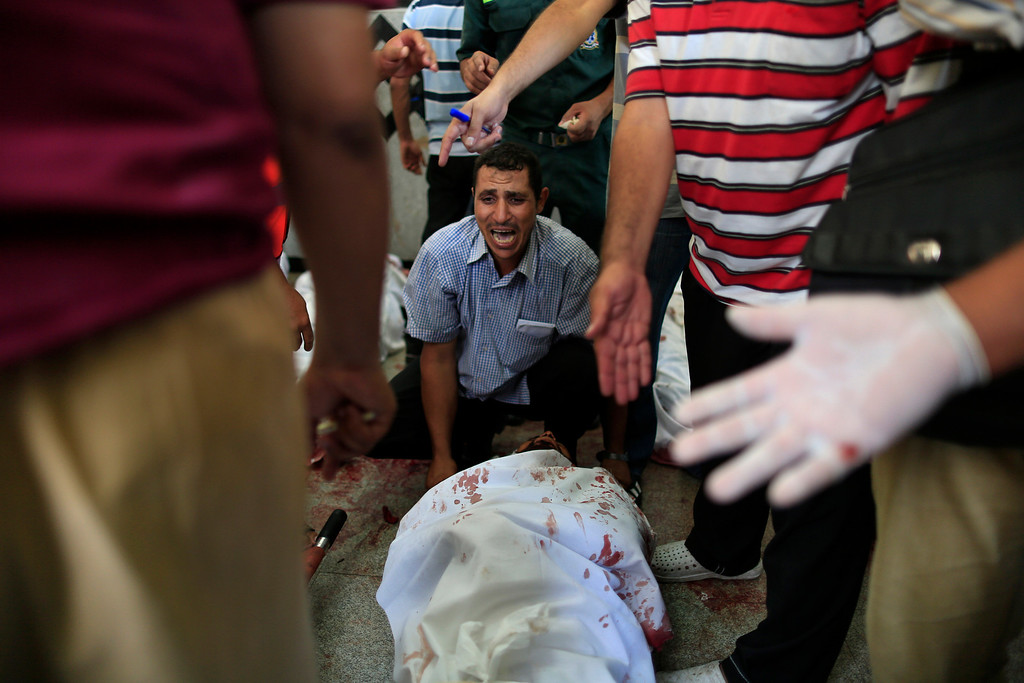 . An Egyptian man sits beside his comrade, a supporter of Egypt\'s ousted President Mohammed Morsi, injured during clashes with security forces at Nasr City, where pro-Morsi protesters have held a weeks-long sit-in, in a field hospital in Cairo, Egypt, Saturday, July 27, 2013. Overnight clashes between security forces and supporters of Morsi in east Cairo left scores of protesters dead and hundreds injured following a day of massive pro-military rallies backing a tough hand against Morsiís backers and the Muslim Brotherhood group from which he hails. (AP Photo/Hassan Ammar)