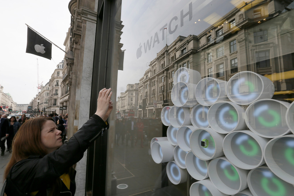 . A woman takes a picture of an Apple Watch on display in the window of the Apple store on Regent Street in London, Friday, April 10, 2015. The technology company\'s latest product is on display in the store ahead of its full release for sale on April 24. (AP Photo/Tim Ireland)
