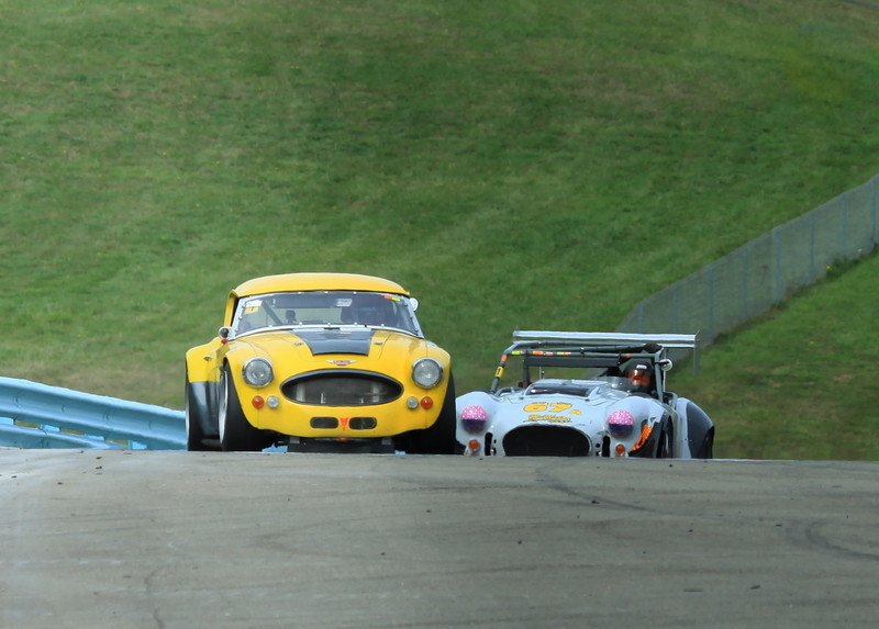 """Austin Healy and Factory Five Racing Cobra, playing """"tag"""" on track at Watkins Glen International"""