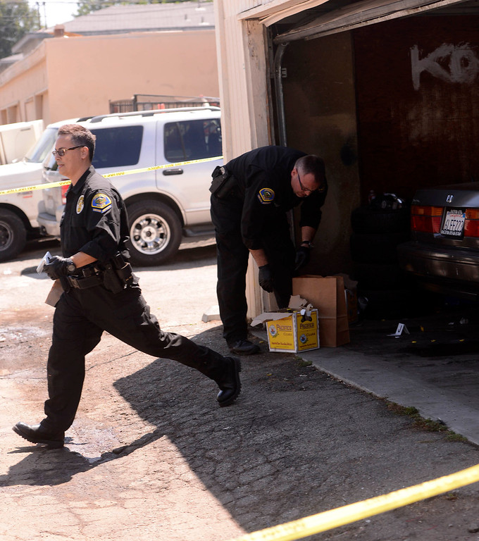 . Pomona Police forensic specialists gather evidence from a double-shooting along the 300 block of Orchid Lane in Pomona August 11, 2013.   GABRIEL LUIS ACOSTA/STAFF PHOTOGRAPHER.