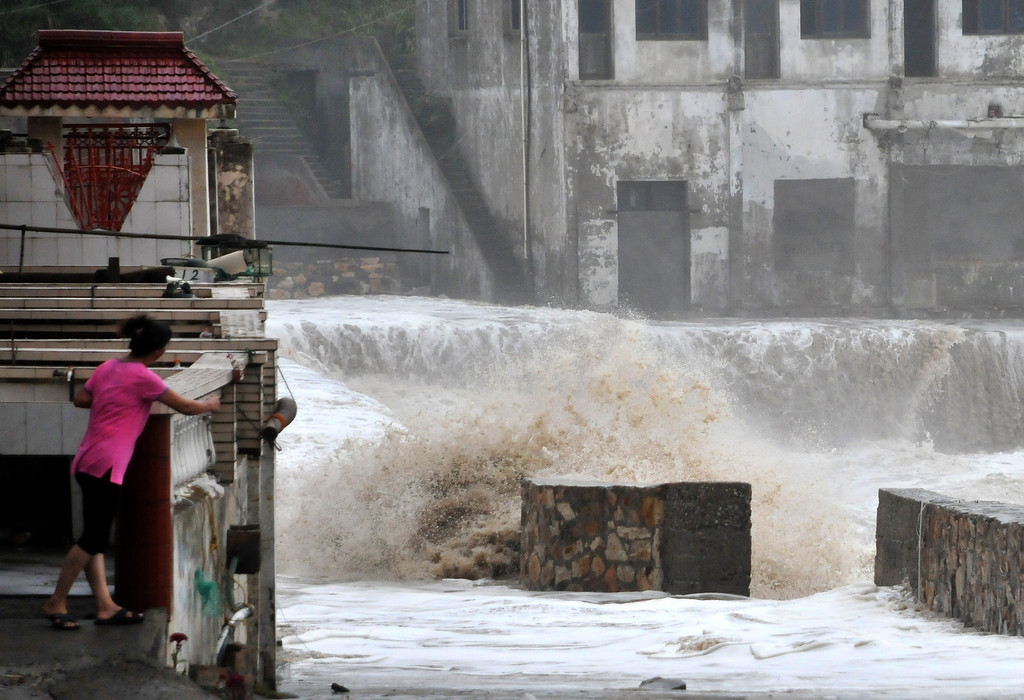 . A woman looks on as a huge wave hits the dike as Typhoon Fitow moves to make its landfall in Wenling, east China\'s Zhejiang province on October 6, 2013.  China was on its highest alert for Typhoon Fitow on October 6, with tens of thousands evacuated as the storm was set to slam into the east coast.   STR/AFP/Getty Images